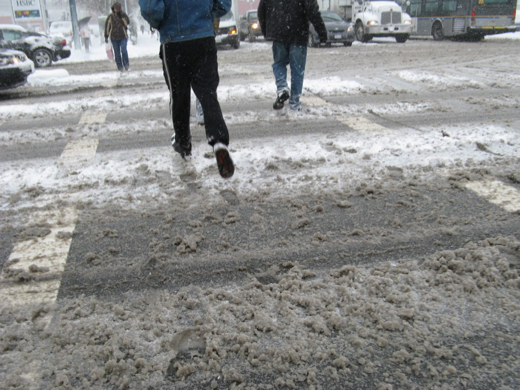 Able bodied people crossing a snow covered major intersection in Vancouver, BC.