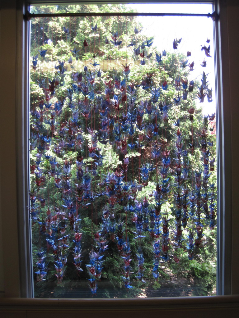 This image shows the origami cranes of Pearson hanging in a window.
