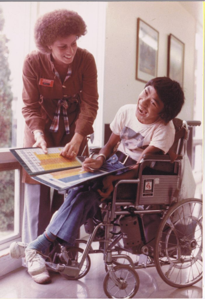 Teenage John sharing a laugh with a Pearson staff member.
